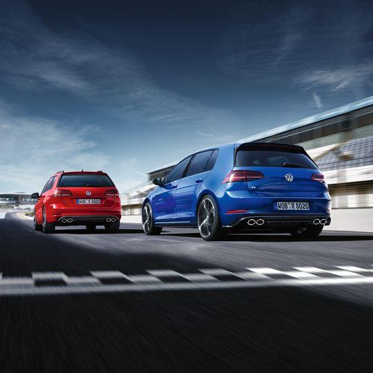 Vista trasera de un Golf GTI rojo y un Golf R azul acelerando en la salida de una pista de carreras