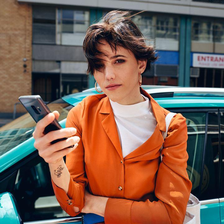 Chica con un móvil en la mano mirando a la cámara frente a un Volkswagen T-Cross turquesa