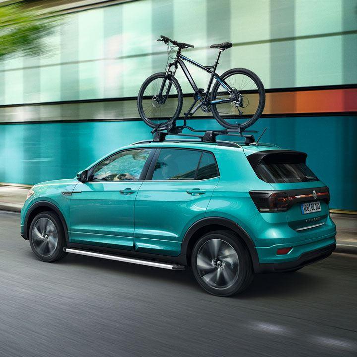 Volkswagen T-Cross turquesa avanzando por la carretera con un soporte para bicicletas en el techo