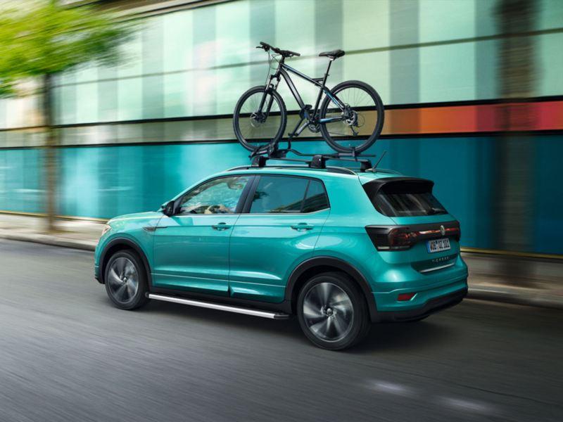 Volkswagen T-Cross turquesa circulando por la ciudad con unportabicicletas