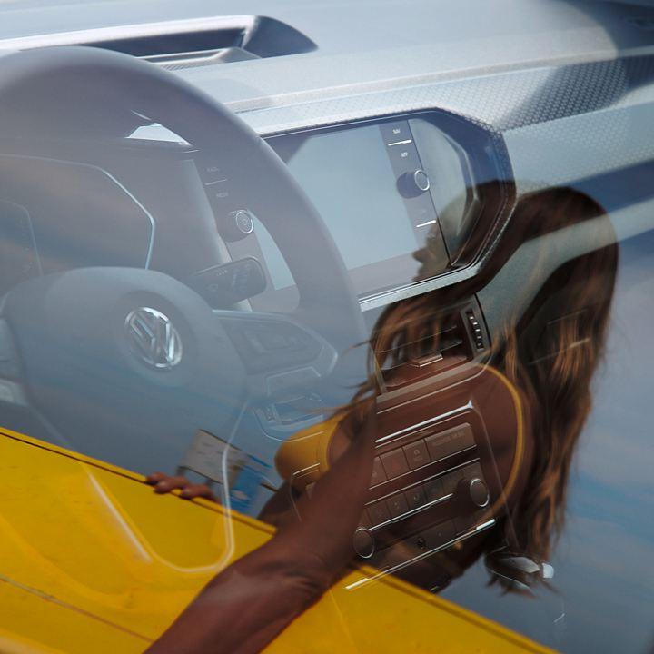 Reflejo de una chica con una tabla de surf amarilla sobre el cristal de un Volkswagen
