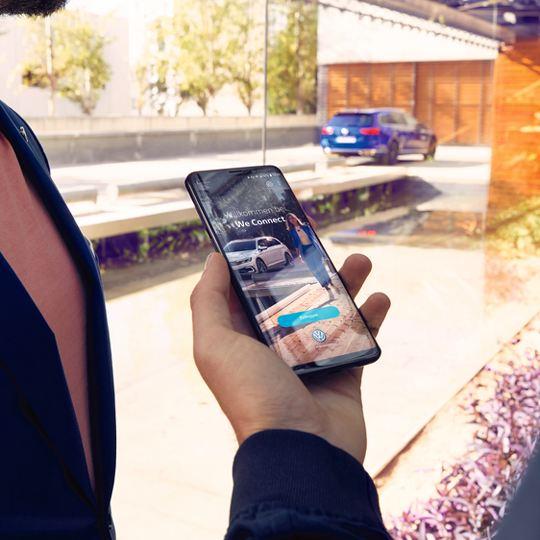 Hombre sosteniendo un móvil donde se ve la app de Volkswagen We, de fondo se ve un Passat Variant azul