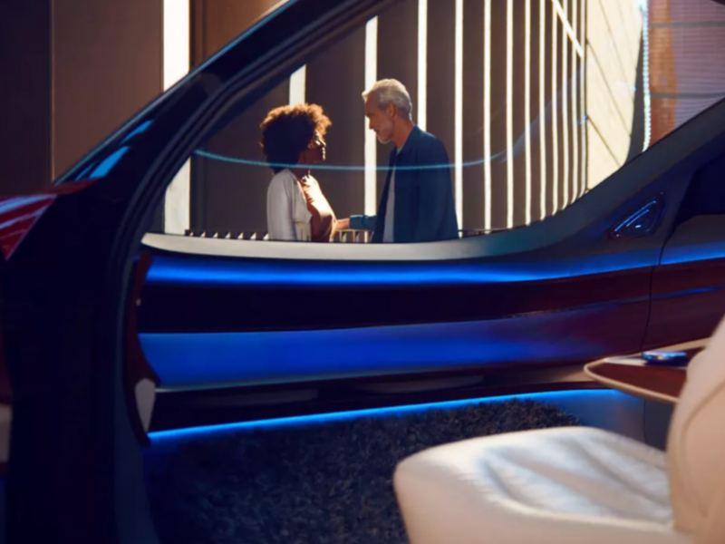 Una mujer y hombre hablando vistos desde dentro de un coche a a través de la ventanilla abierta