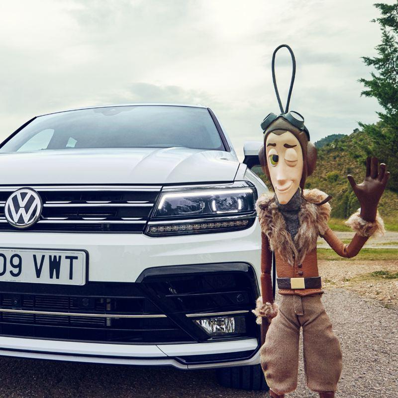 Volkswagen Tiguan blanco aparcado en el campo con un muñeco delante, quiero un Tiguan