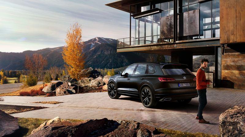 Hombre joven con un Volkswagen Touareg negro aparcado frente a una casa con vista a la montaña