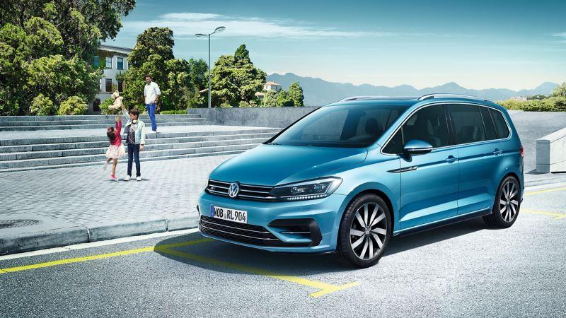Volkswagen Touran azul caribe aparcado frente a una plaza con un padre y dos niños detrás