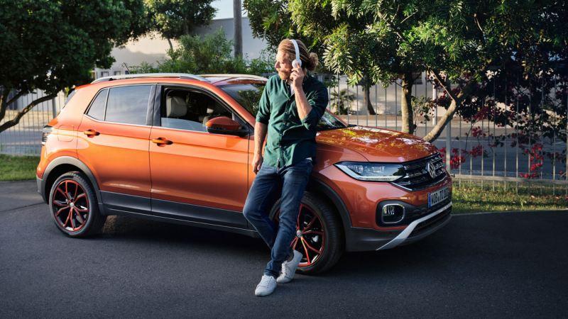 Hombre joven escuchando música con unos auriculares apoyado en un Volkswagen T-Cross naranja