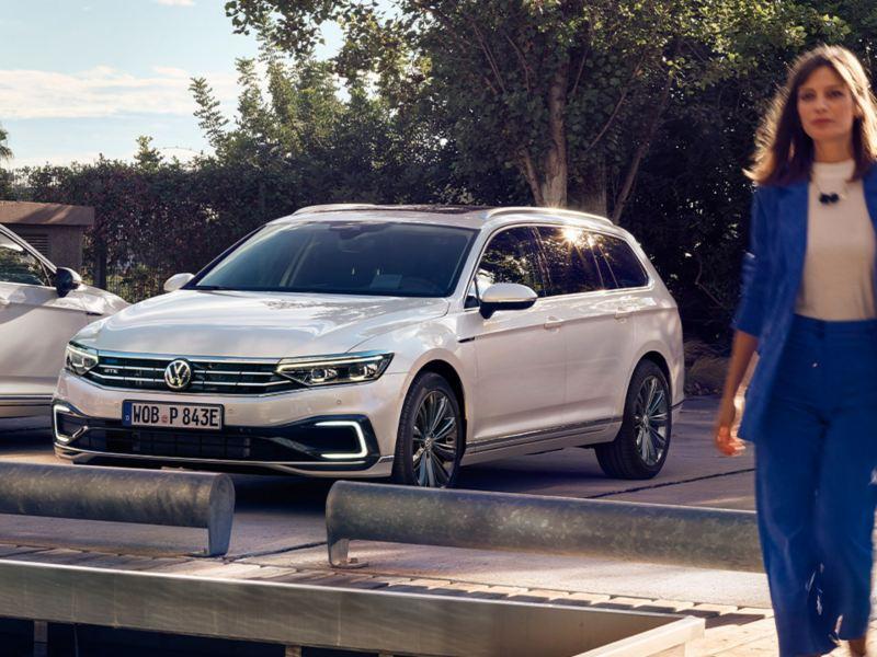 Mujer joven delante de un Volskwagen Passat GTE Variant aparcado