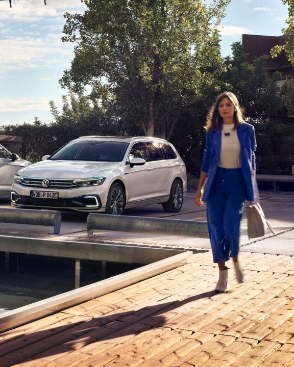 Volkswagen Passat blanco aparcado con una mujer vestida de azul caminando delante