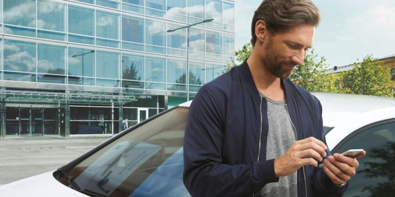 Detalle de las manos de un hombre usando en móvil y apoyado en un Volkswagen azul