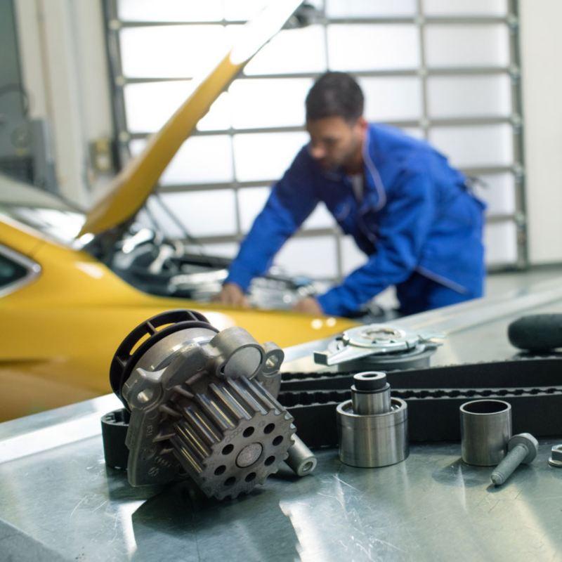 Primer plano de piezas de recambio delante de un hombre de azul reparando un Volkswagen