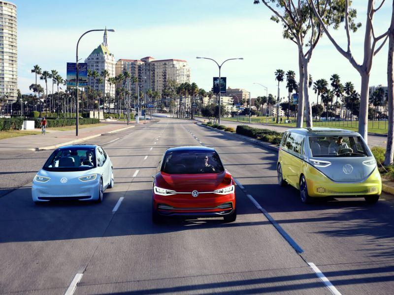 Gama ID circulando juntos por una avenida de día con árboles y edificios de fondo