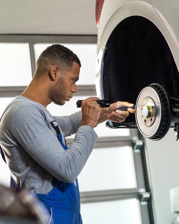 Mecánico revisando los frenos de un Volkswagen levantado por una grúa