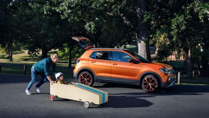 Padre jugando con su hijo en un coche de juguete delante de un T-Cross naranja con el portón trasero abierto