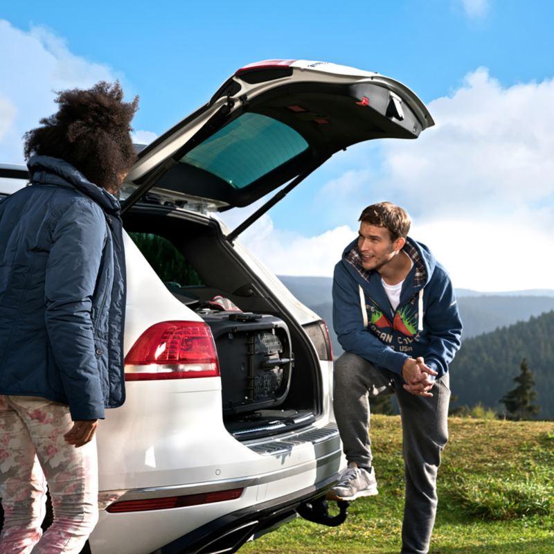 Dos hombres jóvenes en la montaña hablando junto a la parte trasera de un Volkswagen SUV blanco con el portón abierto