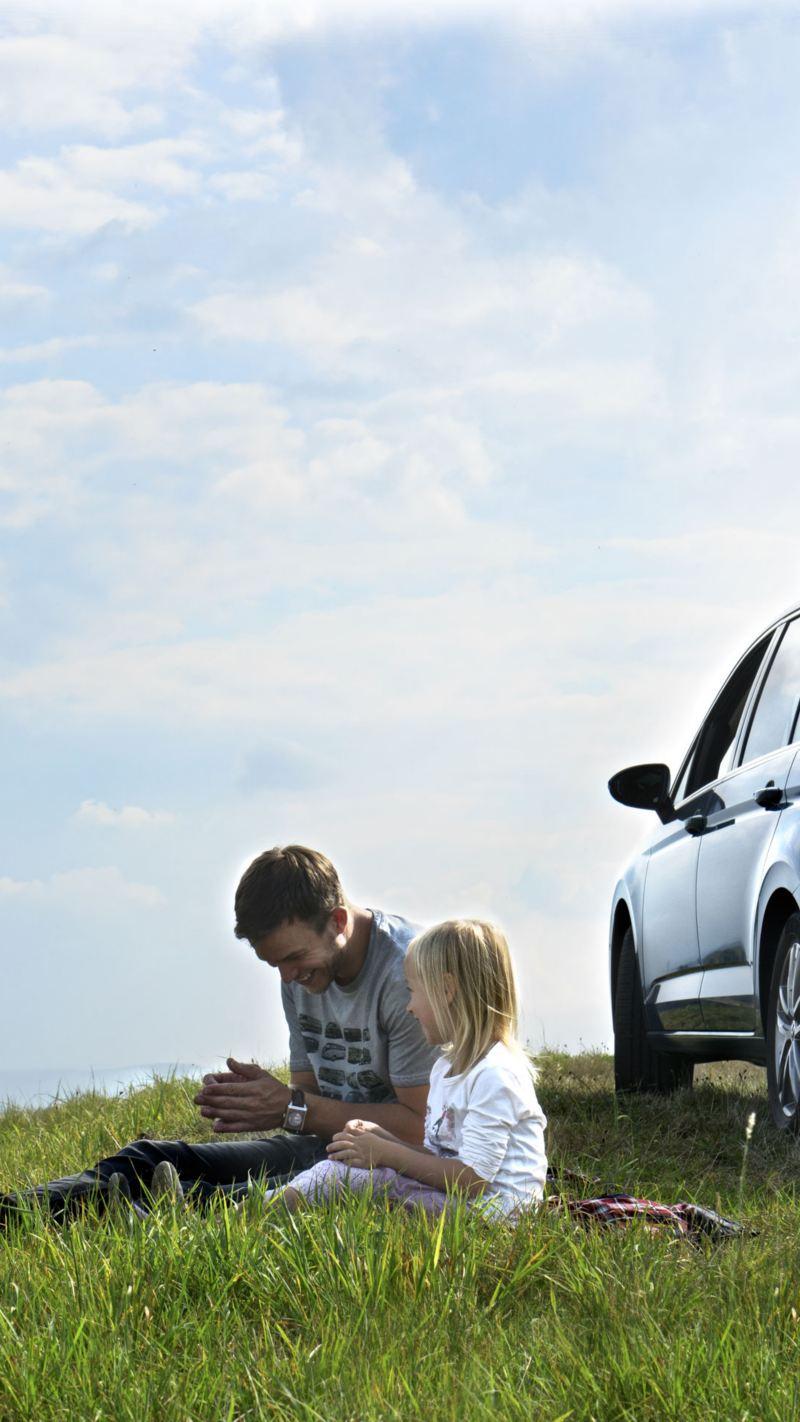 Padre con hija sentados en el campo delante de un Volkswagen SUV azul con el portón trasero abierto