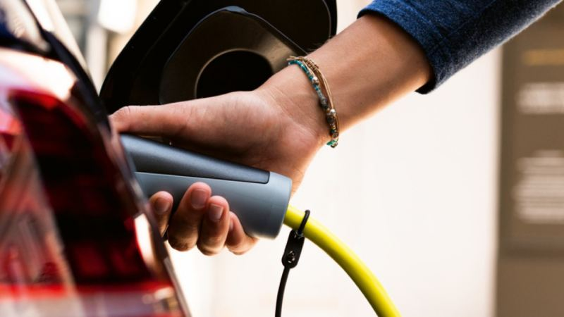 Detalle de una mano sujetando el enchufe de carga híbrida de un Nuevo Volkswagen Arteon