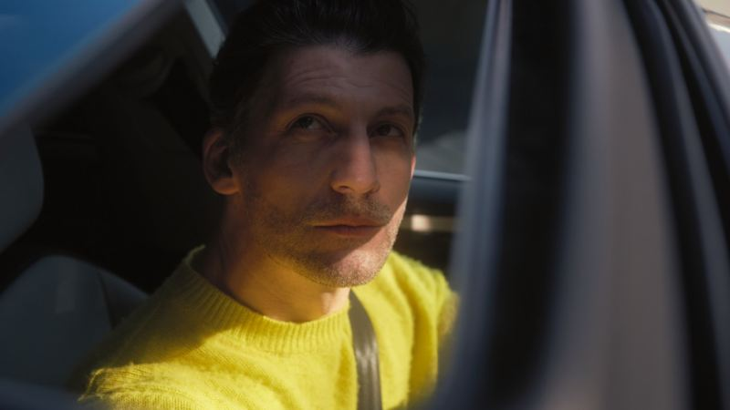 Hombre con un jersey amarillo mirando hacia arriba sentado en el asiento del conductor de un Arteon Shooting Brake