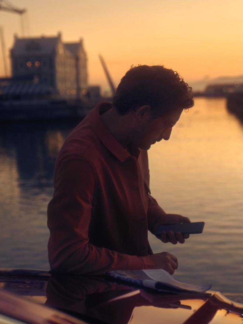 Hombre mirando su móvil apoyado en un Arteon Shooting Brake rojo durante el atardecer en un río