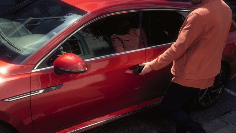 Hombre abriendo la puerta del conductor de un Arteon Shooting Brake rojo