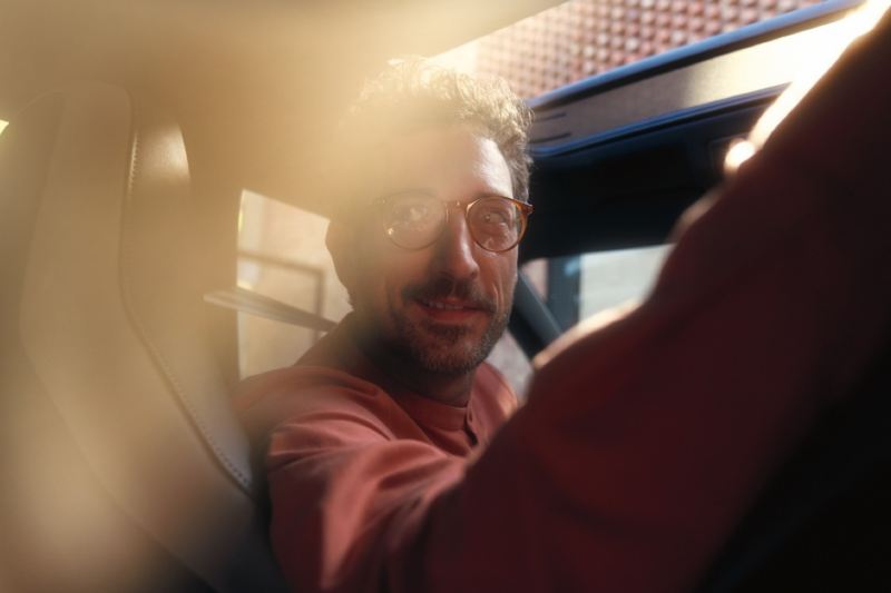 Hombre con gafas girándose sentado en el asiento del conductor de un Arteon Shooting Brake