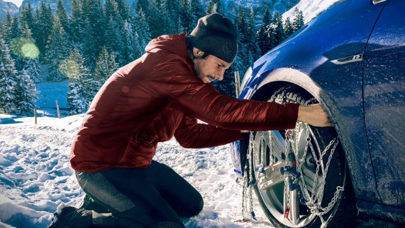 Hombre en un paisaje nevado poniendo cadenas a un Volkswagen azul