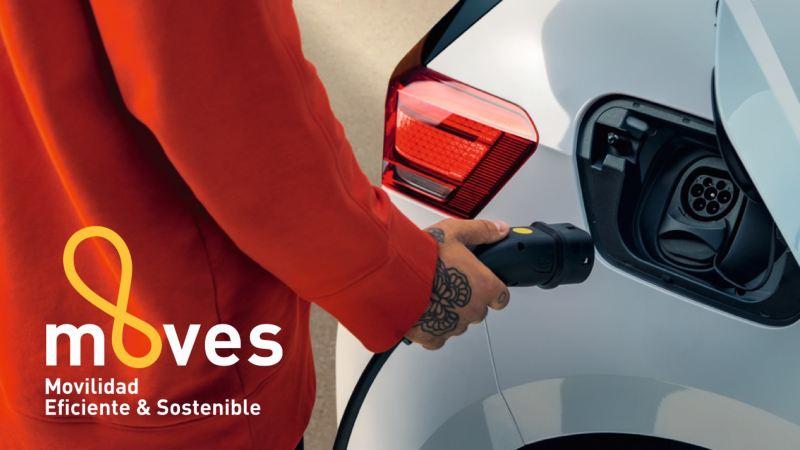 Detalle de una mano conectando un cargador a un Volkswagen eléctrico con el logotipo del plan MOVES
