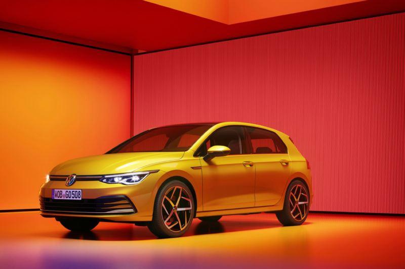 Volkswagen Golf 8 amarillo visto de costado aparcado e iluminado por luces amarillas y naranjas