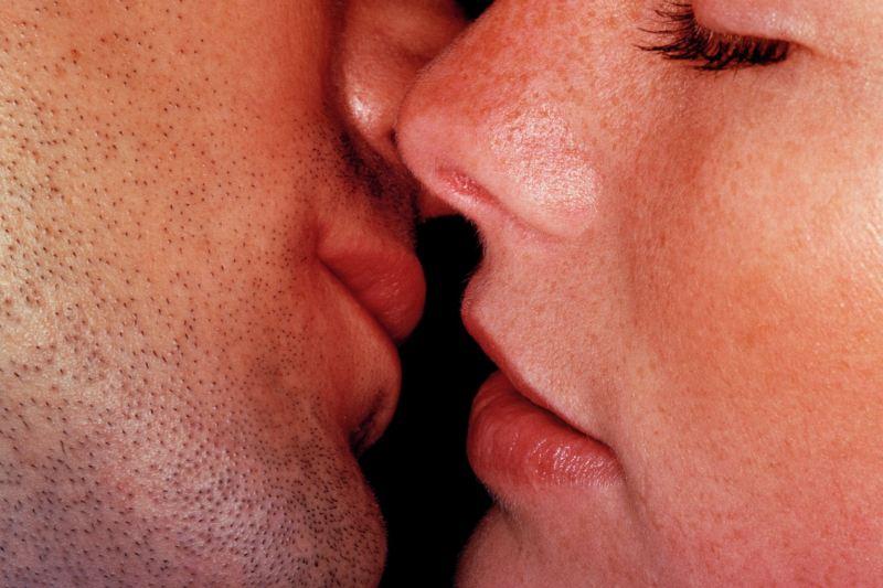 Primer plano de una mujer y un hombre besándose