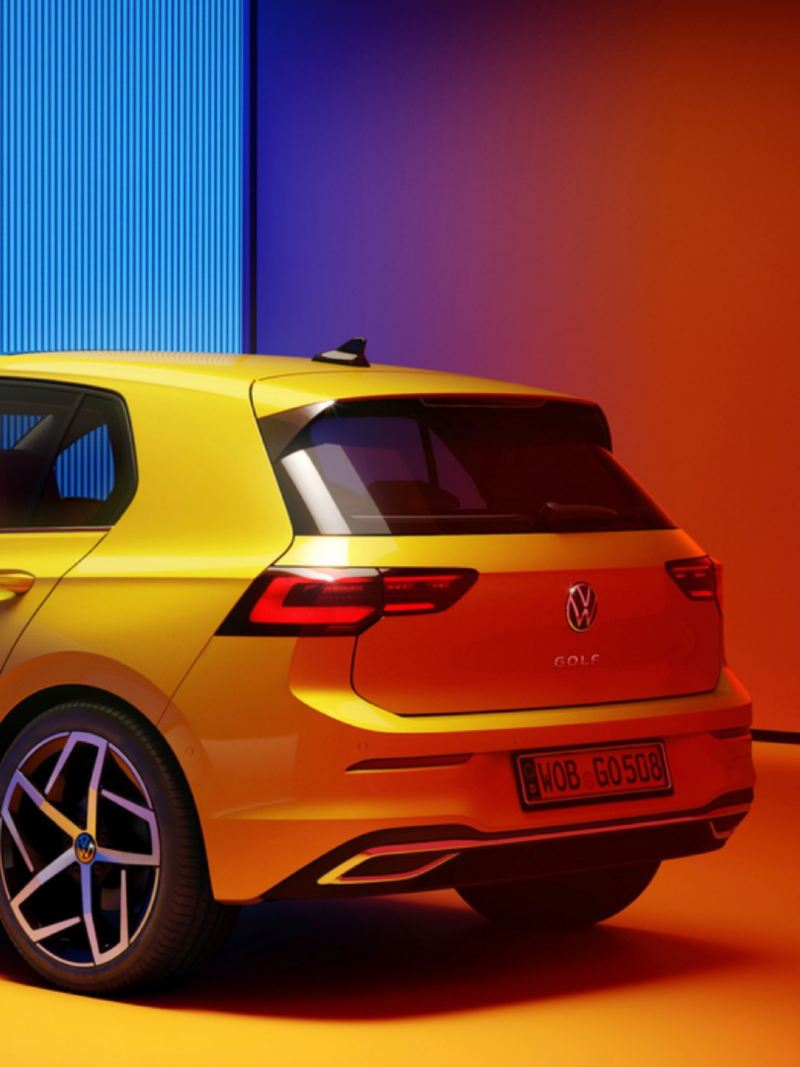 Vista lateral trasera del Volkswagen Golf 8 amarillo aparcado e iluminado por focos