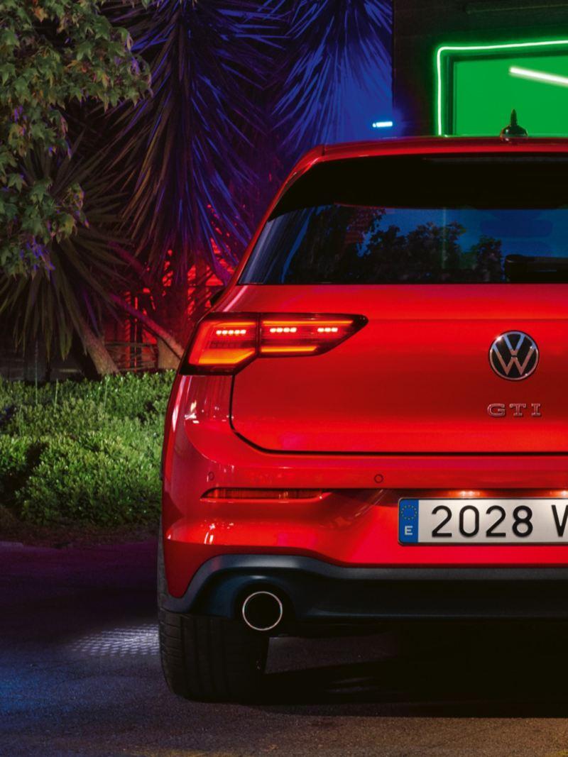 Vista trasera parcial del un Volkswagen Golf 8 GTI rojo aparcado frente a una ventana con luces verdes