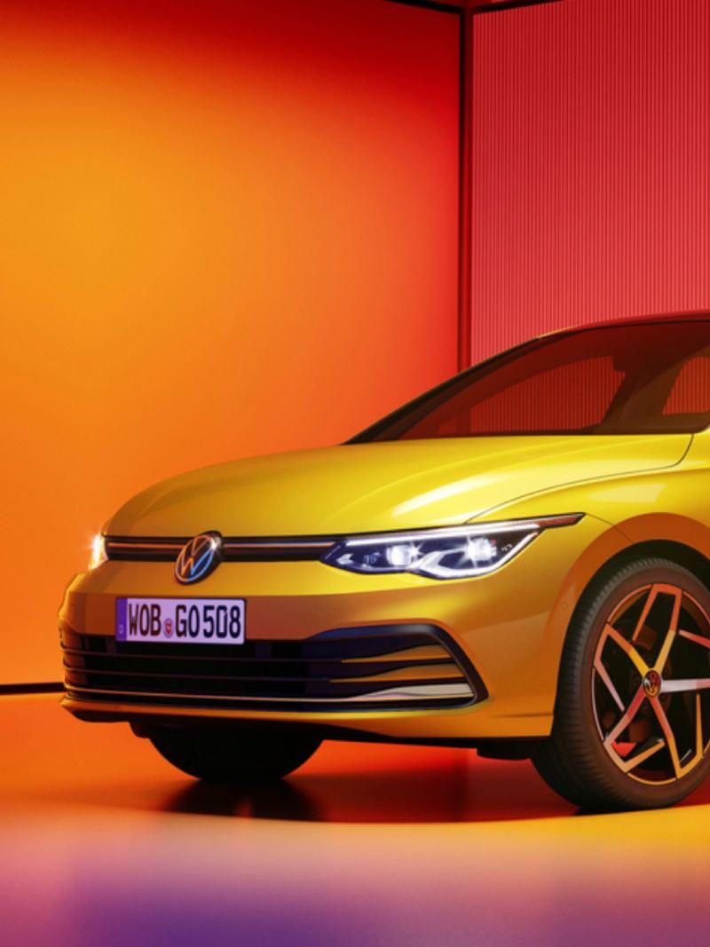Vista lateral frontal del Volkswagen Golf 8 amarillo aparcado e iluminado por focos