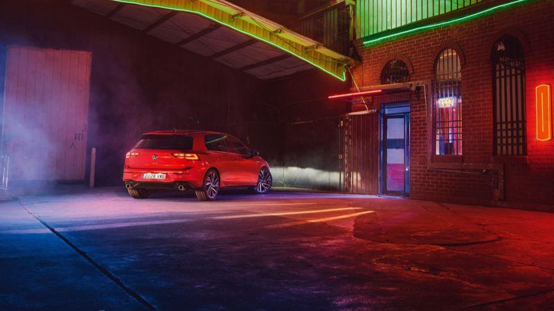 Vista trasera lateral de un Volkswagen Golf 8 GTI rojo aparcado en una nave e iluminado por focos