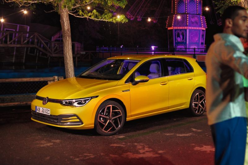 Volkswagen Golf 8 amarillo aparcado en la ciudad de noche
