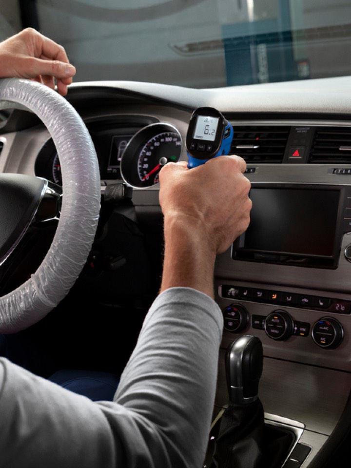 Detalle de las manos de un mecánico revisando el salpicadero de un Volkswagen