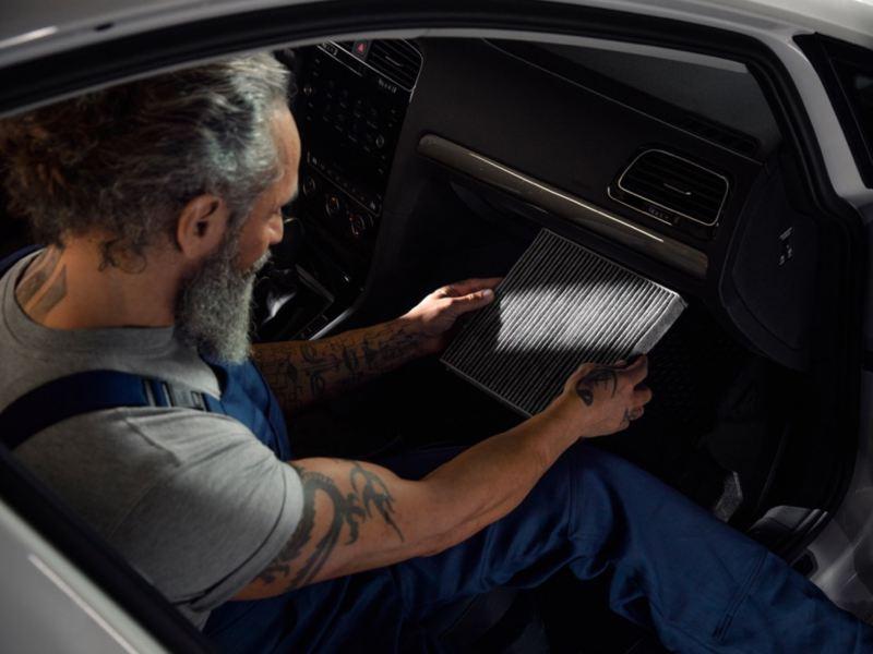 Mecánico cambiando el filtro de aire en el interior de un Volkswagen