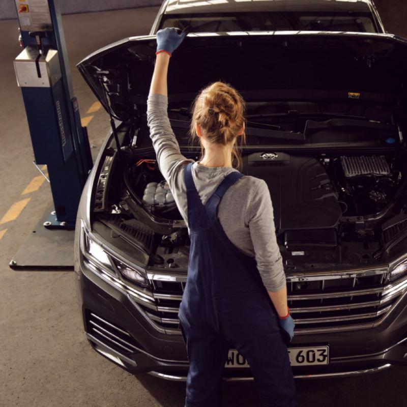 Mecánico visto de espaldas revisando el motor de un Volkswagen en el taller