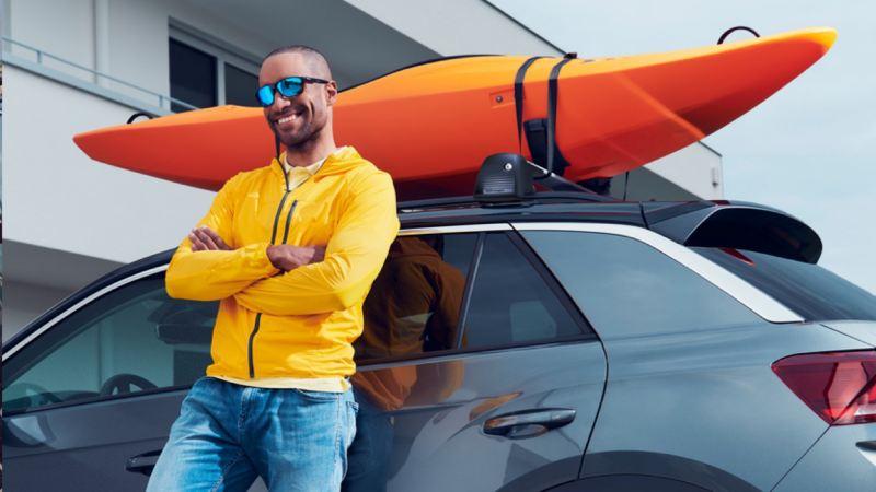 Hombre joven apoyado en un Volkswagen T-Roc con un kayak naranja en el portaobjetos