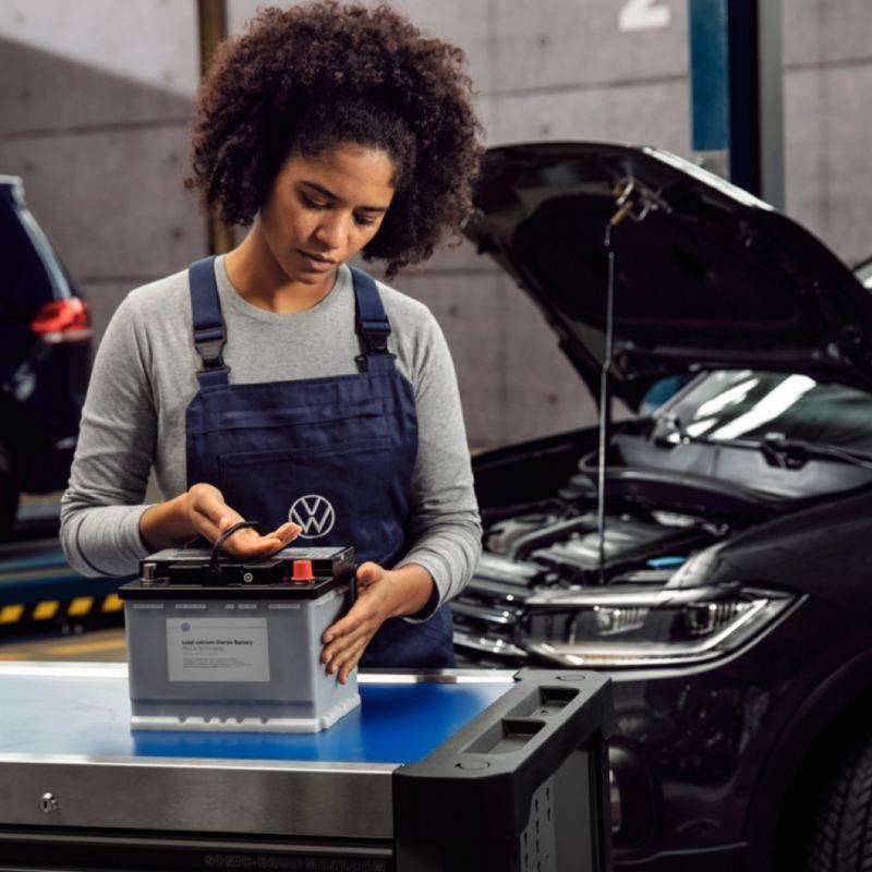 Mecánica revisando la batería de un Volkswagen delante de un coche con el capó abierto