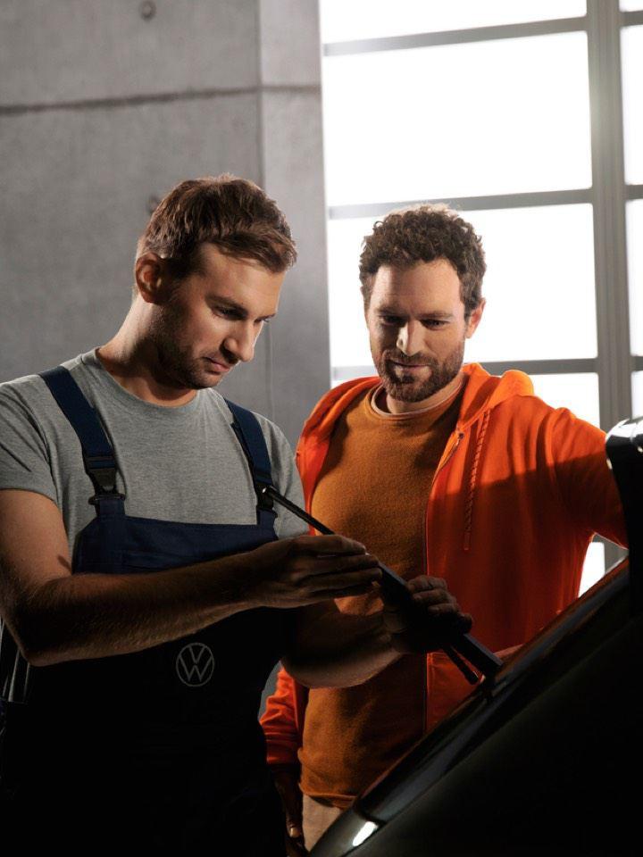 Mecánico cambiando las escobillas del limpiaparabrisas de un Volkswagen mientras un hombre lo observa
