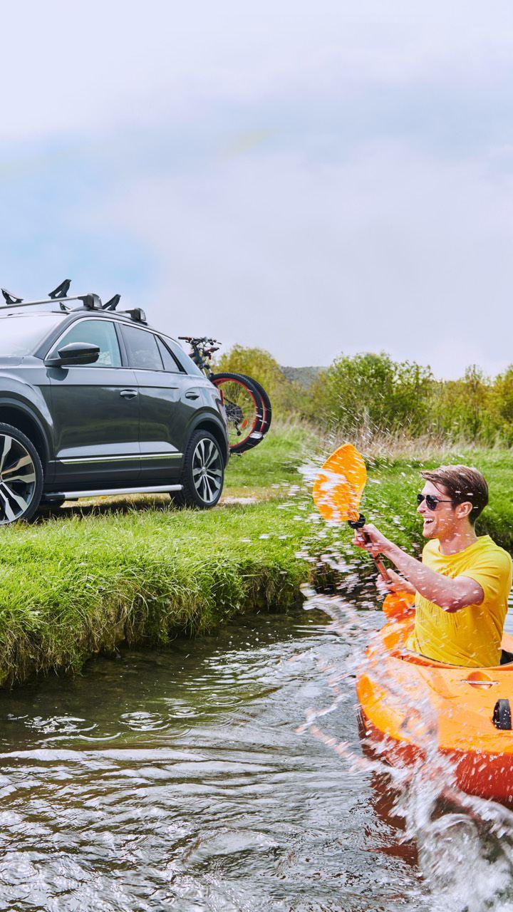 Hombre remando en un kayak en un río delante de un Volkswagen aparcado en la orilla