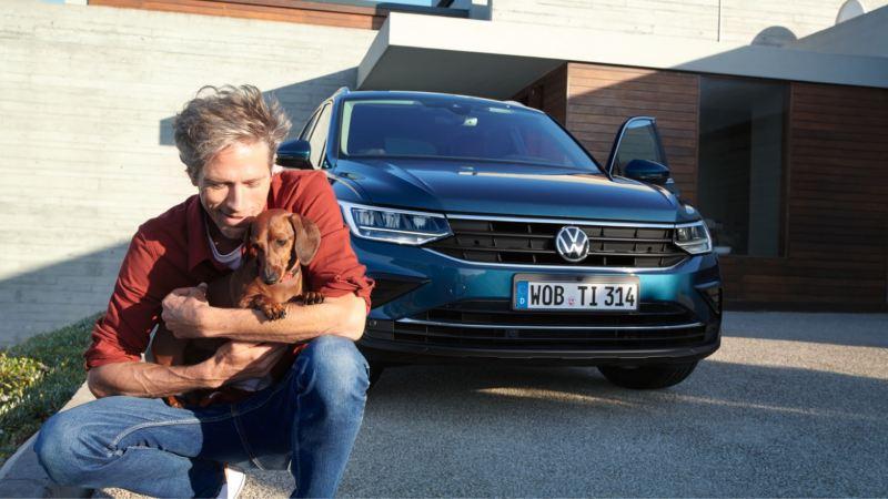 Hombre joven agachado con un perro en brazos delante de un Volkswagen azul aparcado frente a una casa