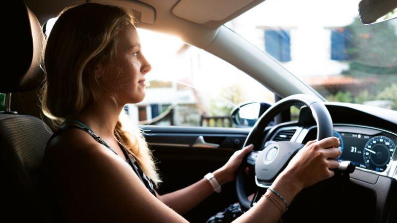 Mujer joven al volante de un Volkswagen