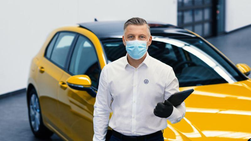 Hombre con mascarilla mirando la cámara delante de un Volkswagen amarillo