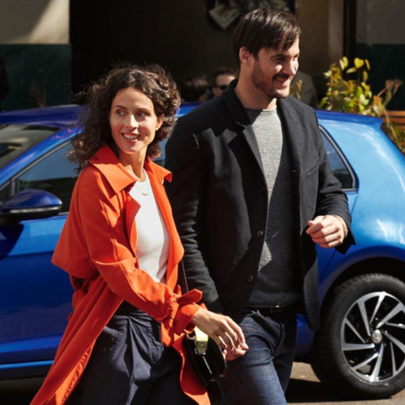 Pareja joven delante de un Volkswagen aparcado en la calle