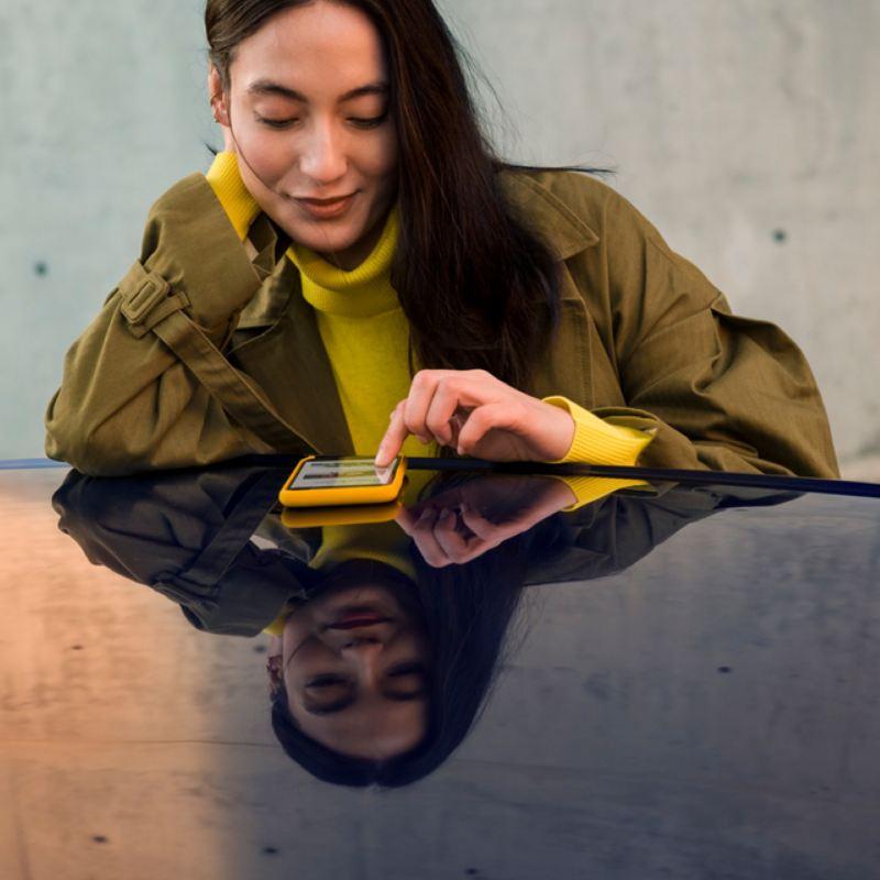 Mujer joven vestida de amarillo usando un móvil apoyada sobre el techo de un coche