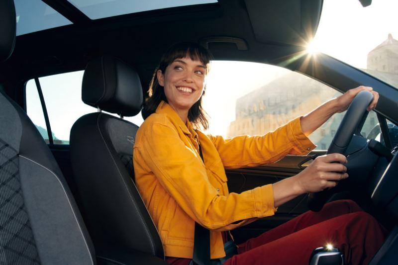 Chica joven sonriendo vestida de amarillo sentada al volante de un Volkswagen
