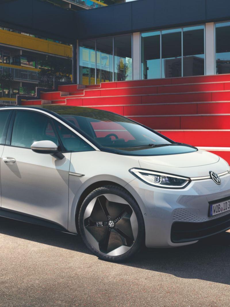 Nuevo Volkswagen ID.3 blanco aparcado en la calle frente a unas escaleras rojas