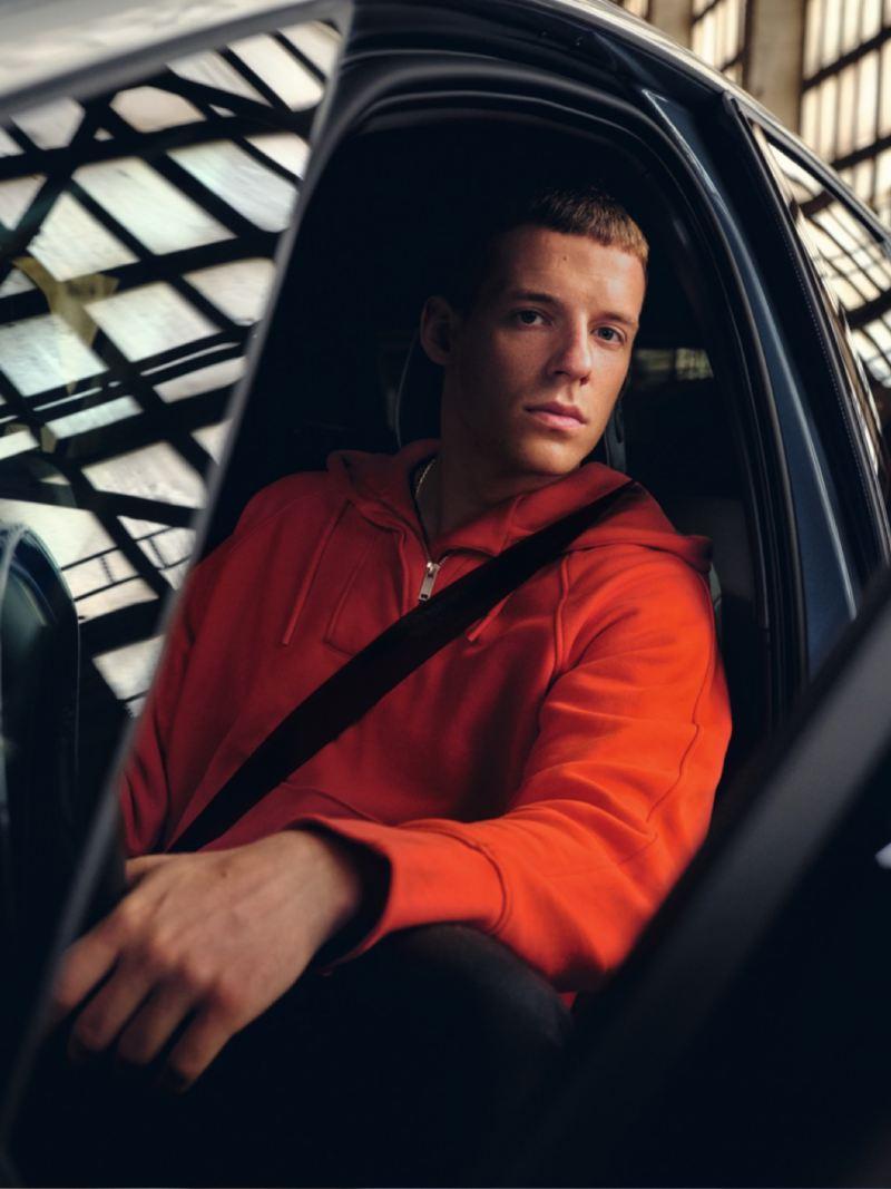 Chico sentado en el asiento del conductor de un Nuevo Volkswagen ID.3 mirando a la cámara