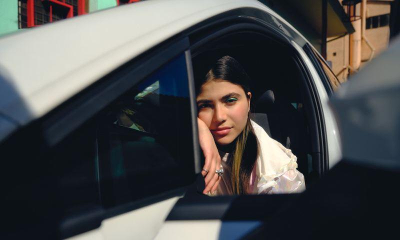 Chica joven dentro de un Volkswagen Golf 8 GTE apoyada en la ventana mirando hacía afuera
